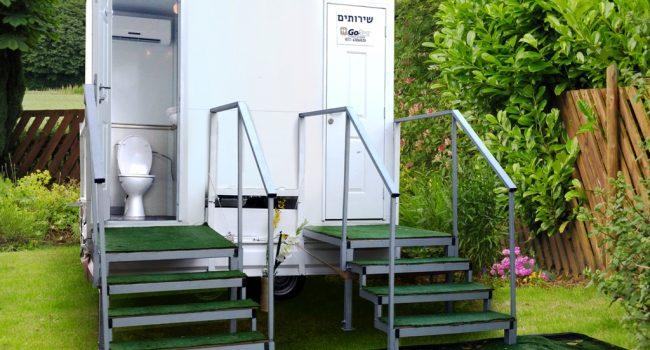 שירותים ניידים 2 תאים על רקע גדר עץ