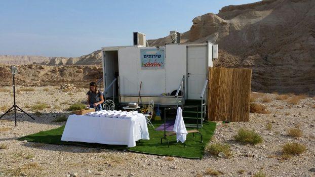 פינת שירותים ניידים ושולחן עם מגבות