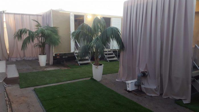 קרונות שירותים עם דשא סינתטי ועציצים