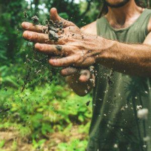 גבר בשטח מחכך את ידיו המלוכלכות אחת בשניה